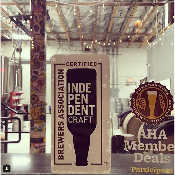 Certified Independent Craft sticker and sign on window with brewery kegs and fermenters